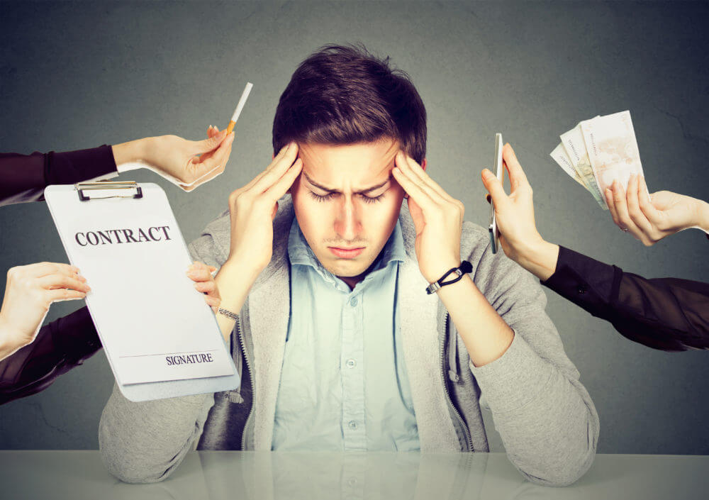 photo of stressed man holding his head with stressors surrounding him