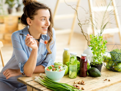 photo of a woman eating a salad, veggies and juice on table