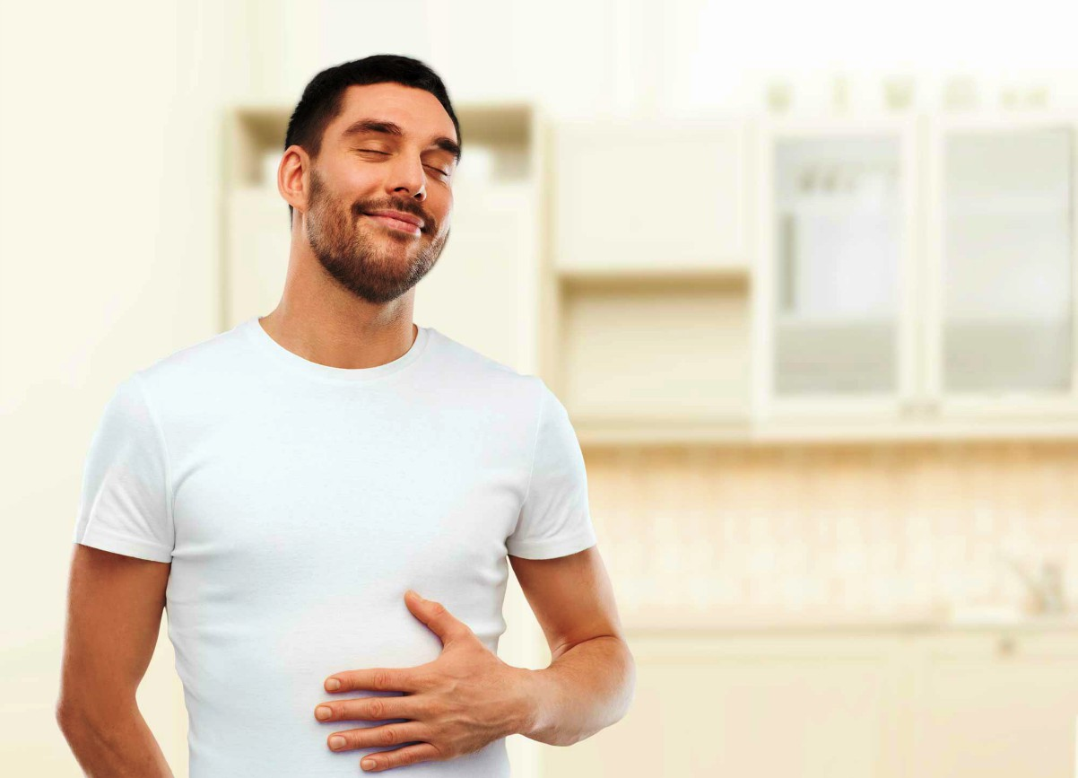 Happy full man touching his tummy over kitchen background | Enzymes… A Health Miracle? | Enzymes