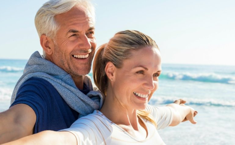 Feature | Happy senior couple standing on beach with arms outstretched | Milk Thistle Detox for Heavy Metals, Chemotherapy, and Radiation