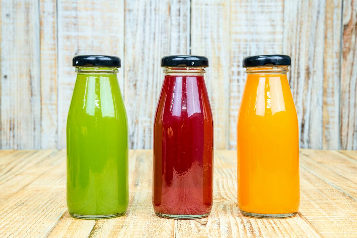 Juice bottle on vintage wooden background | Is The Fructose In Fruit Making You Fat And Sick?