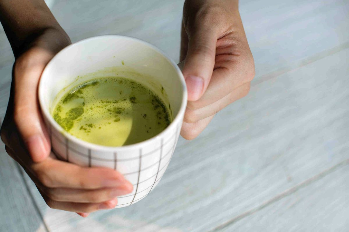 Close up photography of person holding ceramic mug | The Battle Of The Greens: Moringa vs. Matcha | moringa benefits | super greens