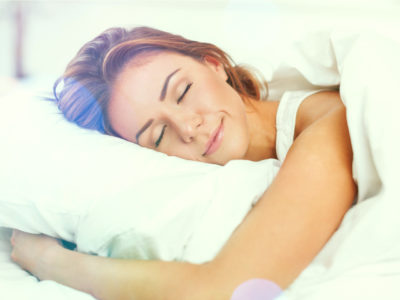 photo of content woman sleeping with arms around pillow