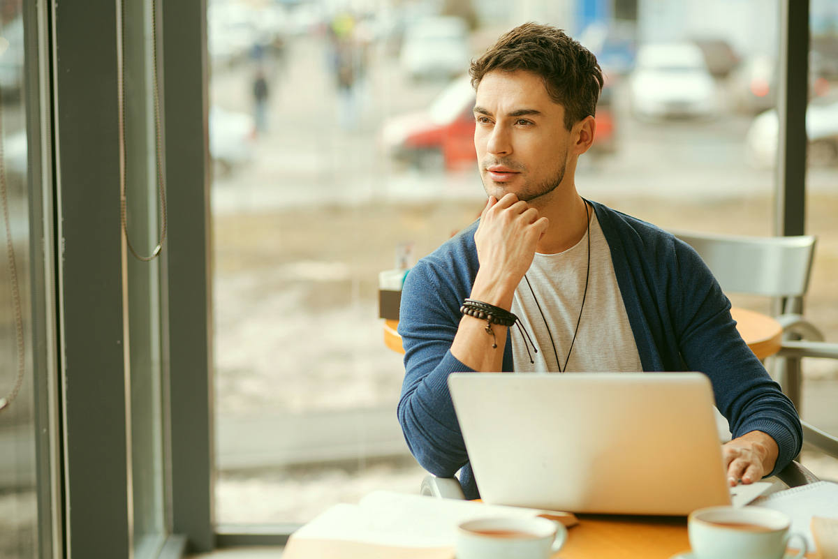 Handsome young guy holding hand on his chin and thoughtfully looking | How To Re-Evaluate Your Relationship With Social Media To Live More Intentionally