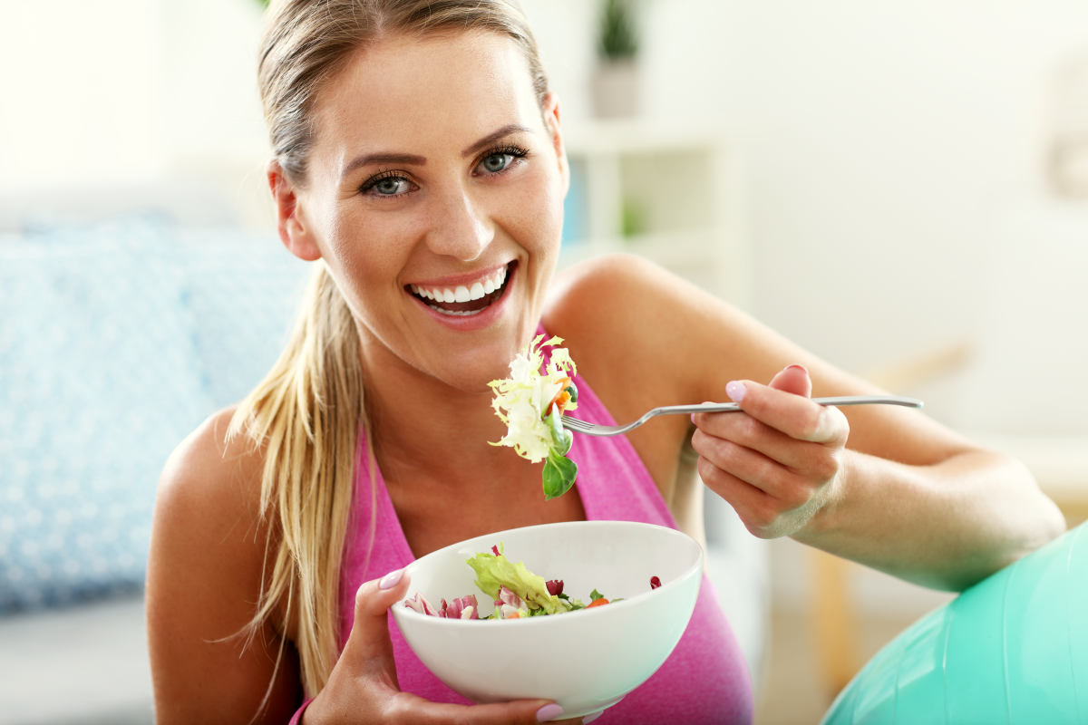 Fit woman eating healthy salad | Ways To Have A Balanced Microbiome