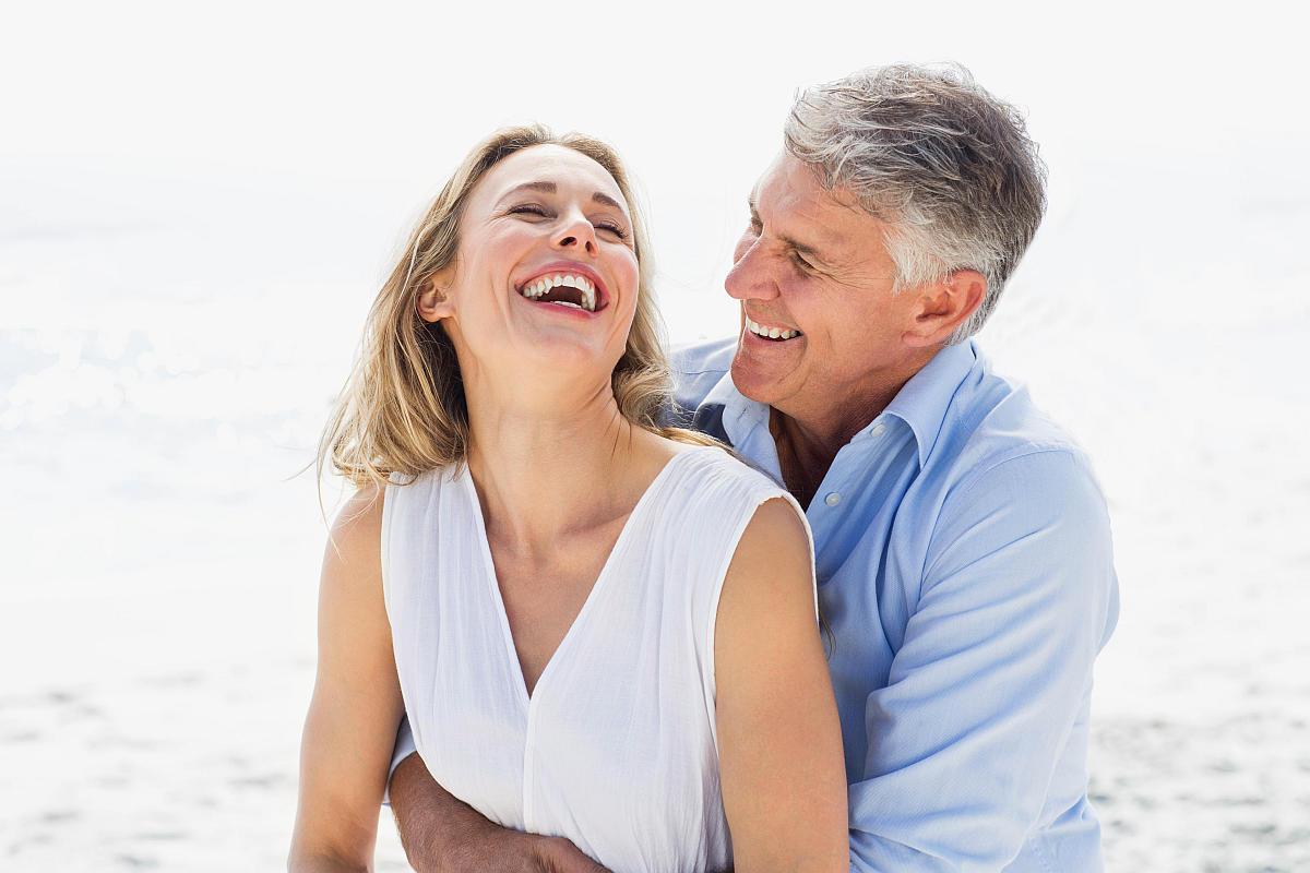 Happy couple laughing together beach | The Battle Of The Greens: Moringa vs. Matcha | moringa benefits | super greens