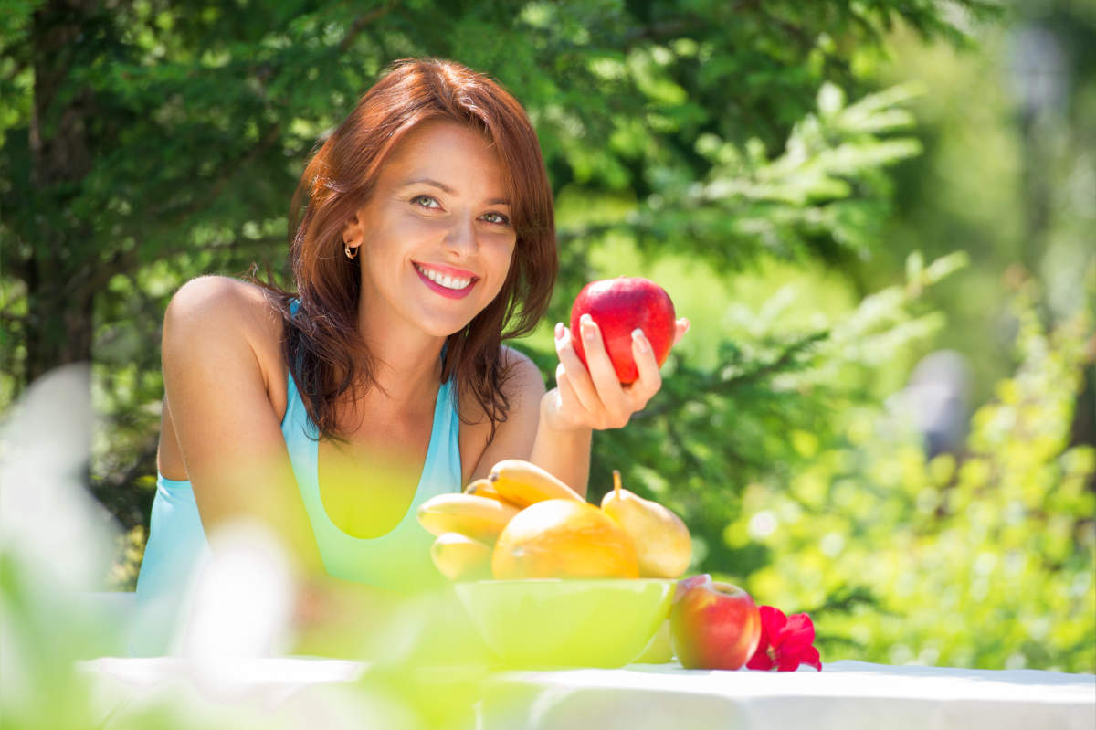 Happy smiling young woman eating organic | How Is Trimethylamine Produced And What Should You Know About It