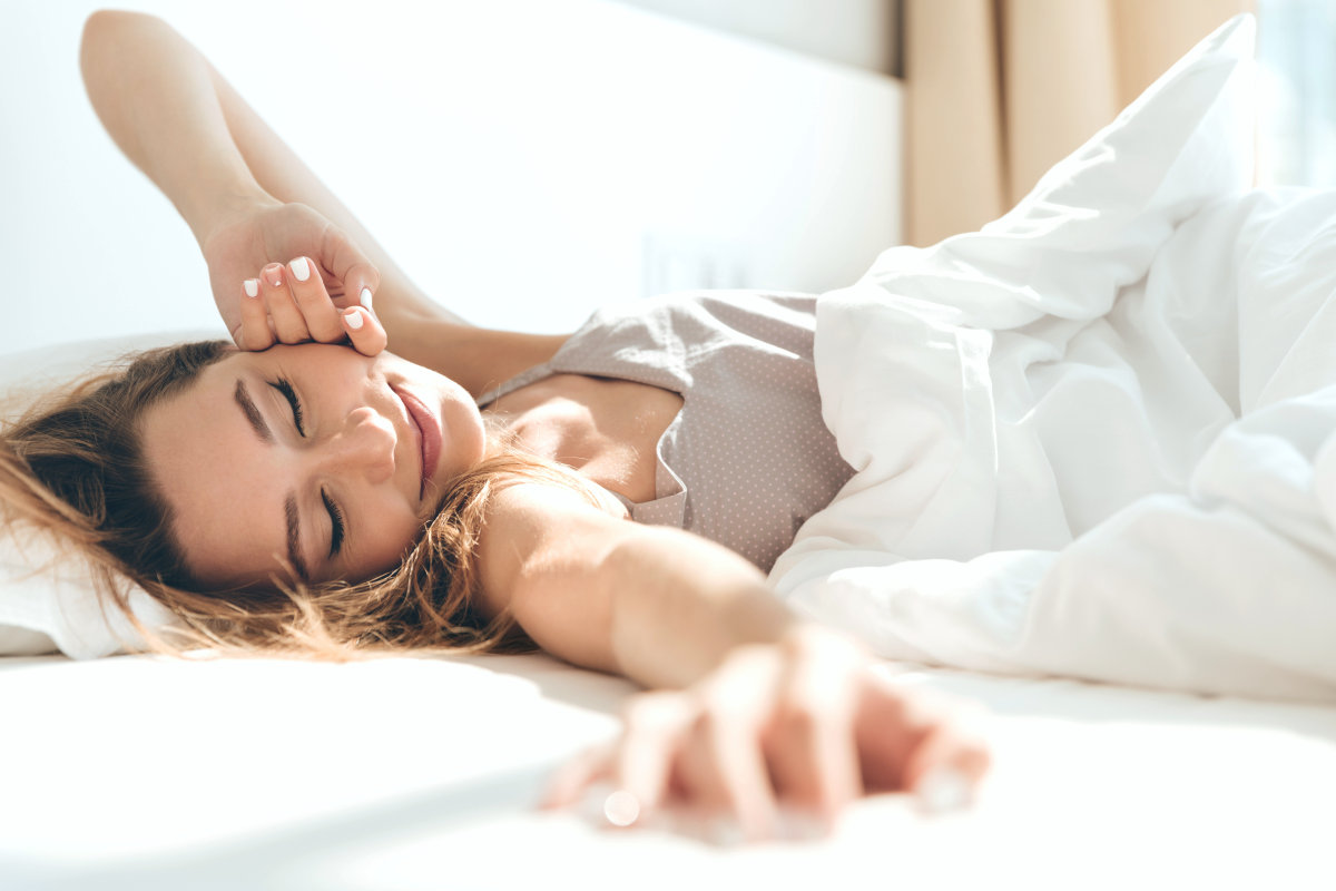 Image of young smiling pretty lady lies in bed indoors | 9 Sleep Tips Arianna Huffington Swears By