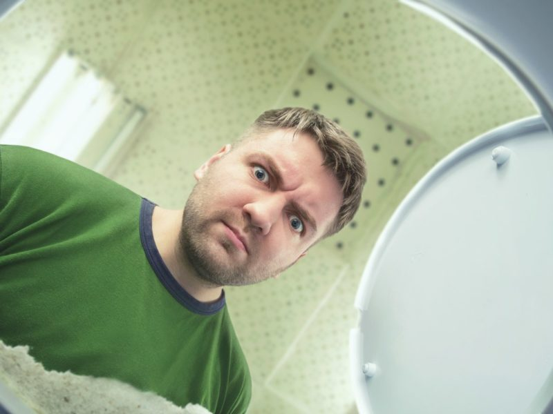 photo of man looking in toilet bowl