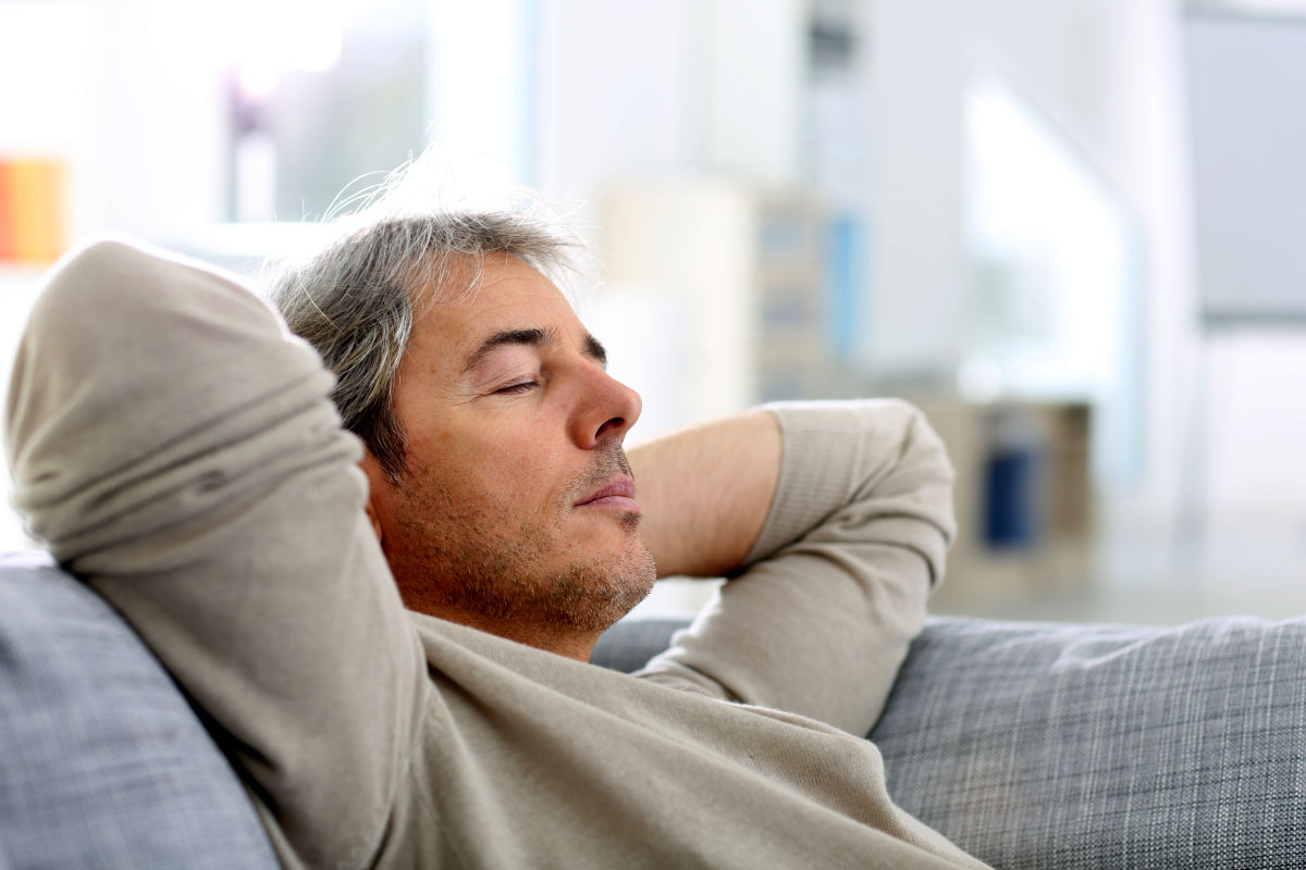 Man taking a nap in sofa at home | 9 Sleep Tips Arianna Huffington Swears By