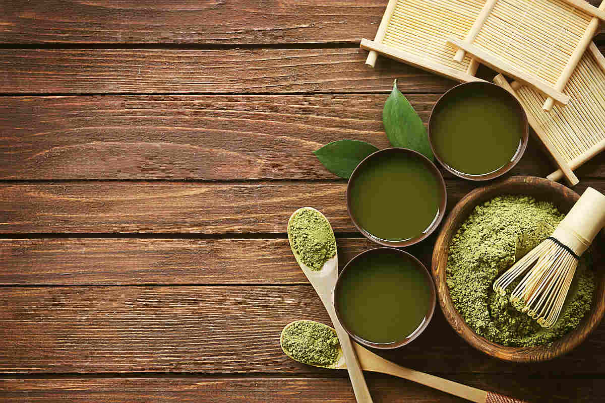 Flat lay of matcha powder and leaves on a table | The Battle Of The Greens: Moringa vs. Matcha | matcha benefits | super greens