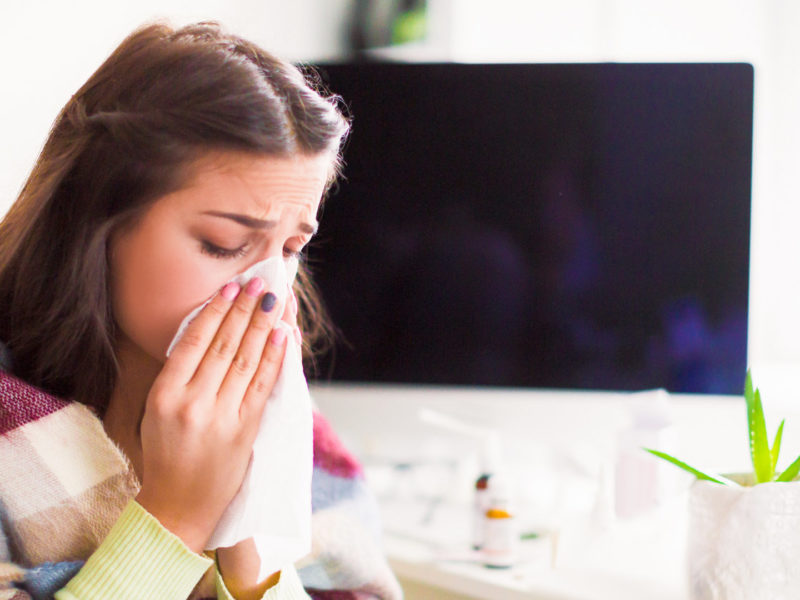 photo of young, sick woman blowing nose