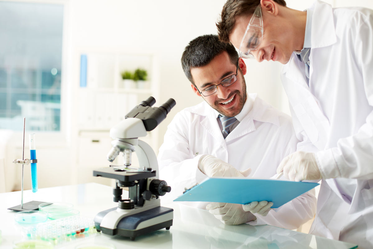 Two clinicians discussing medical document in laboratory | The Relations Between Stress, Trauma, And Autoimmune Conditions | stress