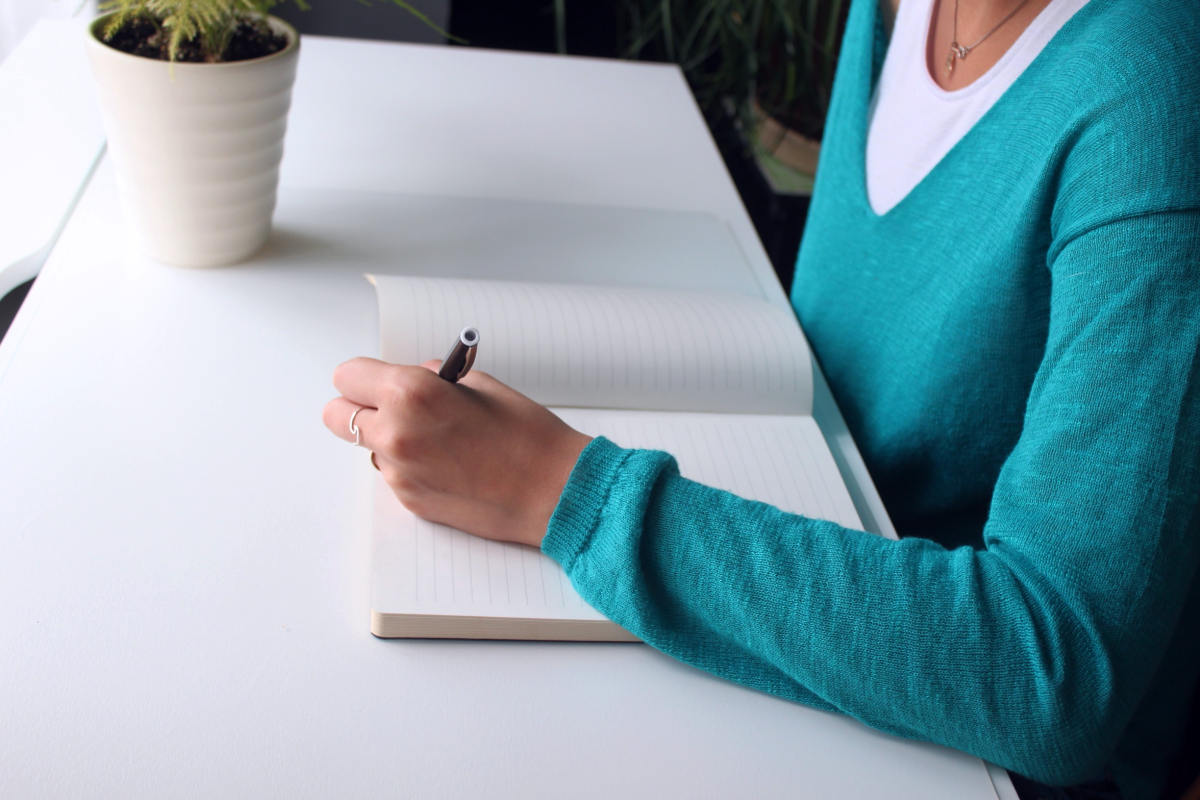 Woman writing on a notebook on a desk | 9 Sleep Tips Arianna Huffington Swears By