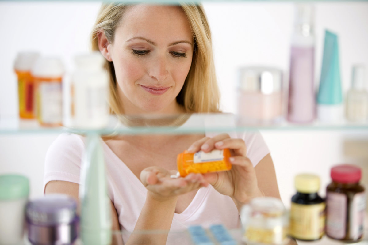 A young woman pours out medicine into her hand | The Relations Between Stress, Trauma, And Autoimmune Conditions | stress