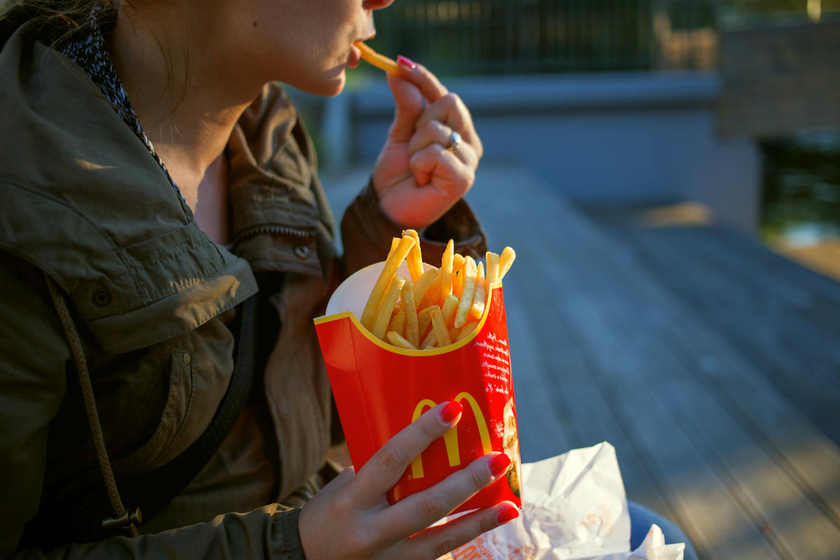 Woman in brown trench coat eating fries | Reasons To Stop Eating Processed Foods And 10 Healthy Swaps