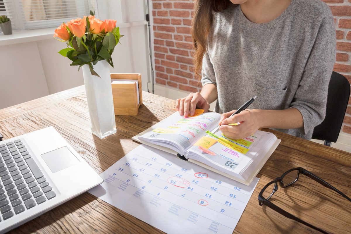 Businesswoman Making Agenda On Personal Organizer | End Procrastination With These 9 Time Management Strategies