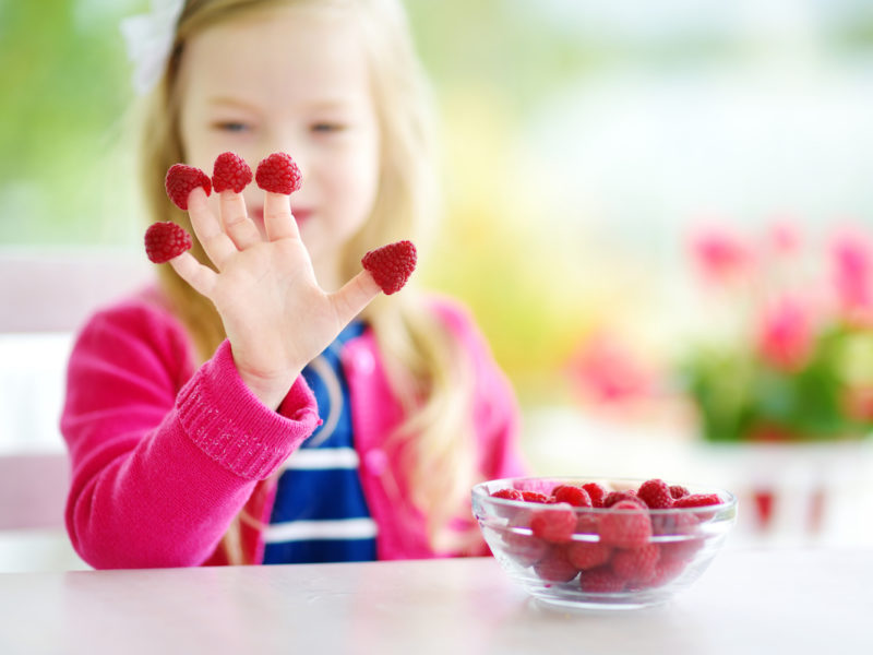 photo of young girl eating raspberries