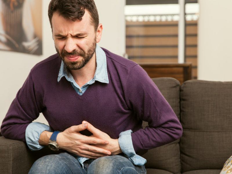 photo of man feeling unwell, holding stomach in pain