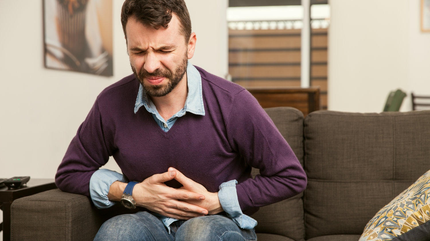 Feature | Guy with a beard feeling unwell with a stomach ache | What Is Leaky Gut Syndrome And How Does It Affect Your Health?