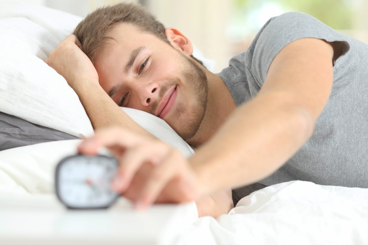 Happy wake up of a happy man lying on the bed | How A Balanced Microbiome Promotes Higher Energy Levels