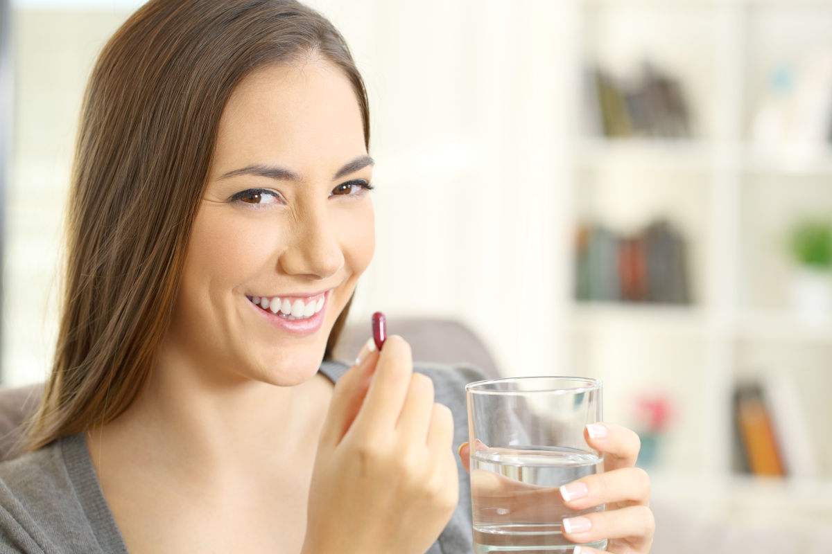 Happy woman looking at camera holding a pill and a glass of water   Natural Brain Vitamins To Improve Your Memory And Focus