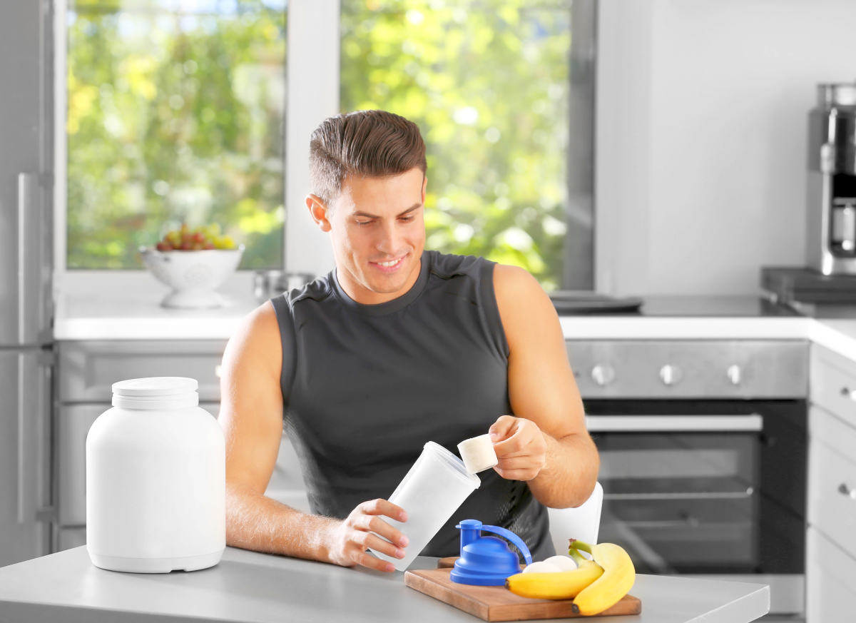 Man preparing protein shake in kitchen | Can Too Much Protein Cause Inflammation?