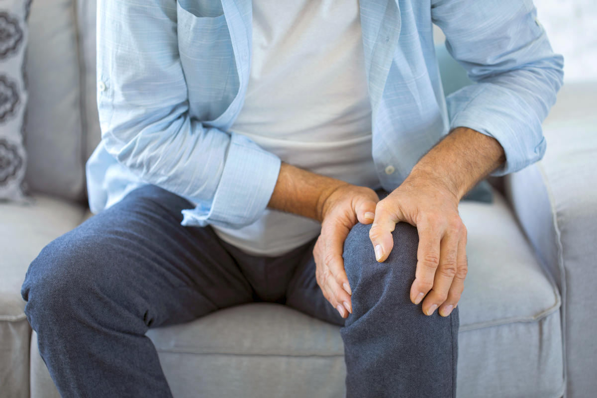 Old man suffering from knee pain sitting sofa | Can Too Much Protein Cause Inflammation?