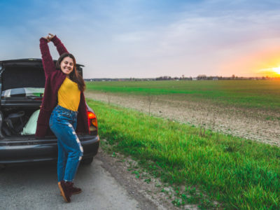 woman stretching in front of car