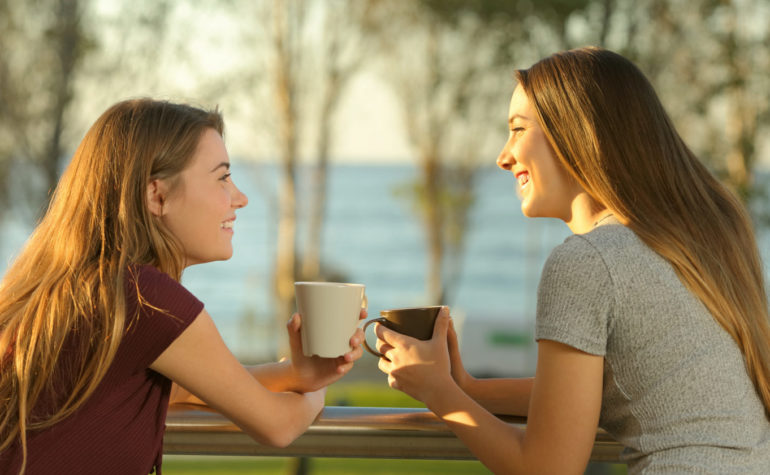Feature | Two happy friends talking outdoors in an apartment balcony | Caffeine Alternatives For A Natural Energy Boost