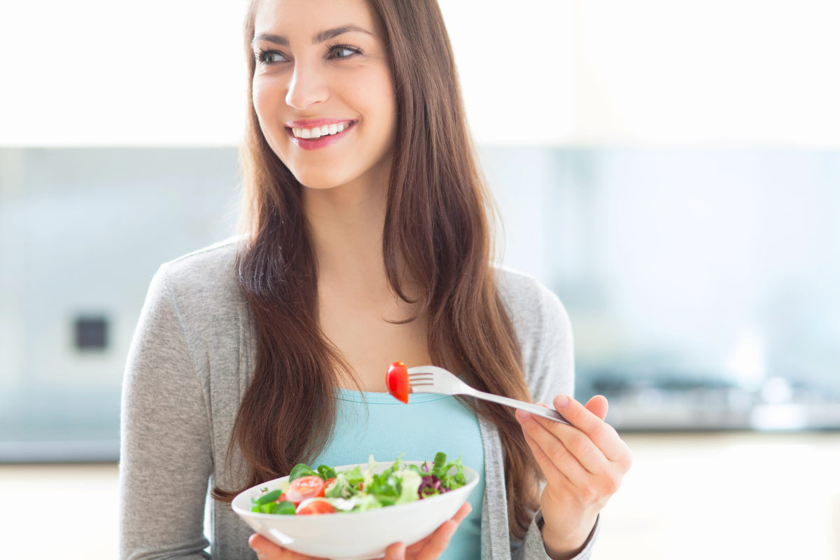 Woman eating salad | How A Balanced Microbiome Promotes Higher Energy Levels