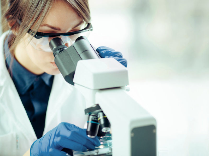 photo of young scientist-looking through microscope in laboratory