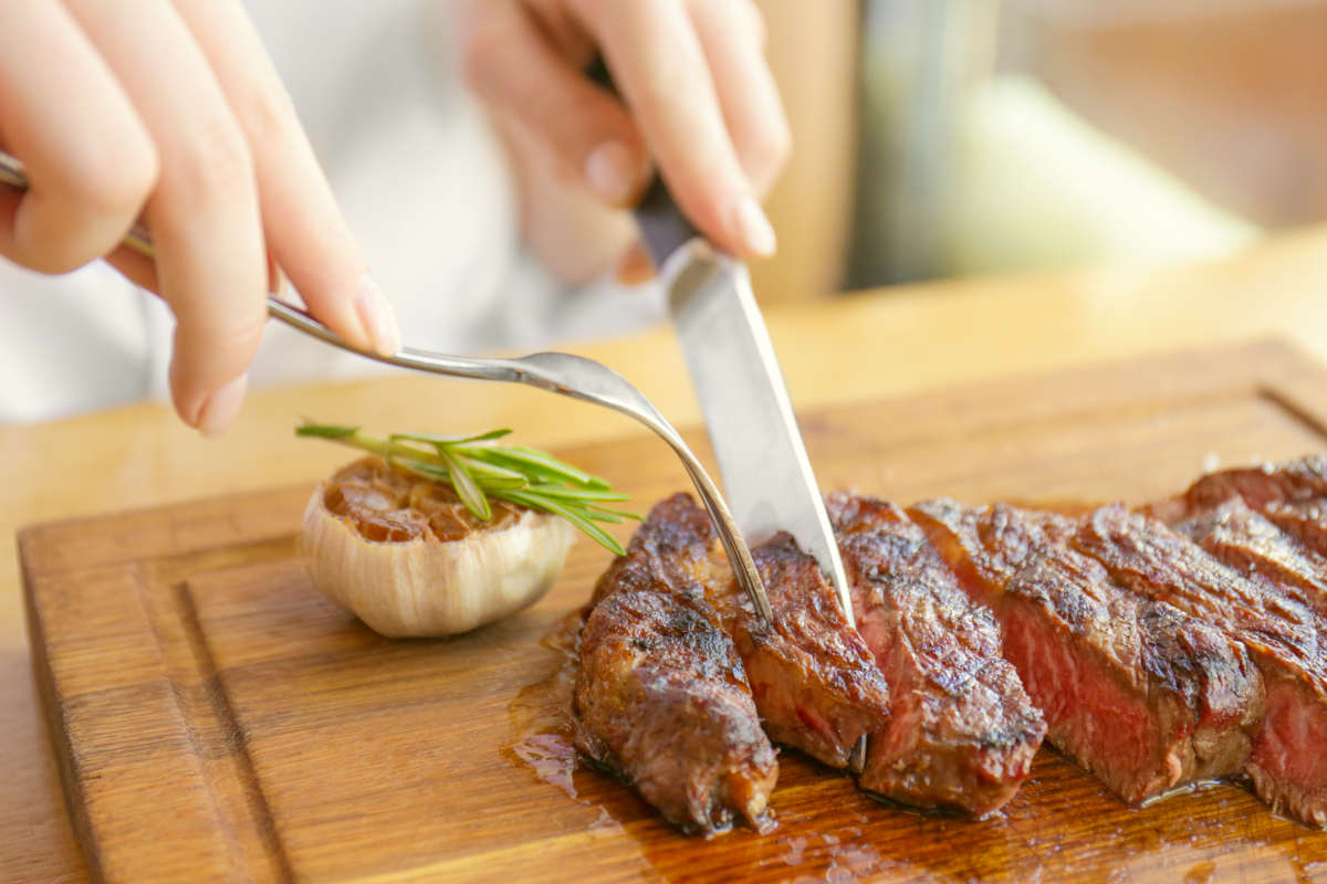 Young woman eating grilled steak in restaurant | Risks Of High TMAO And How To Reduce TMAO Levels