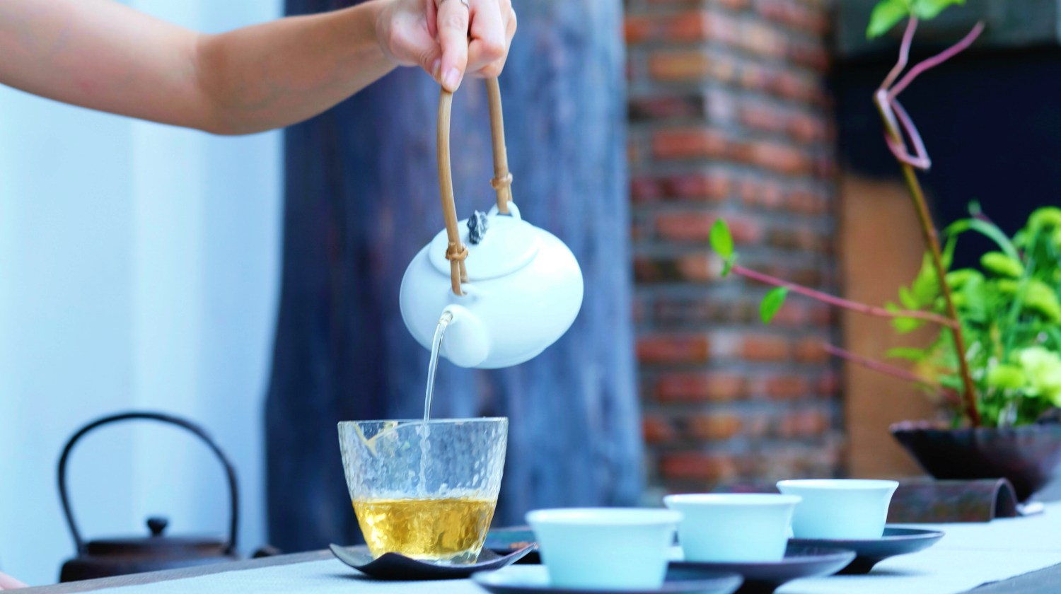 Featured | person pouring green tea | Best Herbs for Energy and Vitality | natural herbs for energy