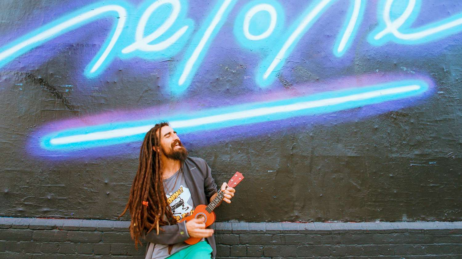 Featured | musician plays in front of grafitti | Tips To Keep The Stress Away During Busy Summer Months | remove stress