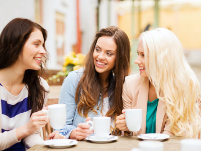 photo of three friends drinking coffee and a cafe