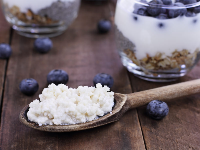 photo of kefir on a wooden spoon with kefir, blueberry, and granola parfaits in the background