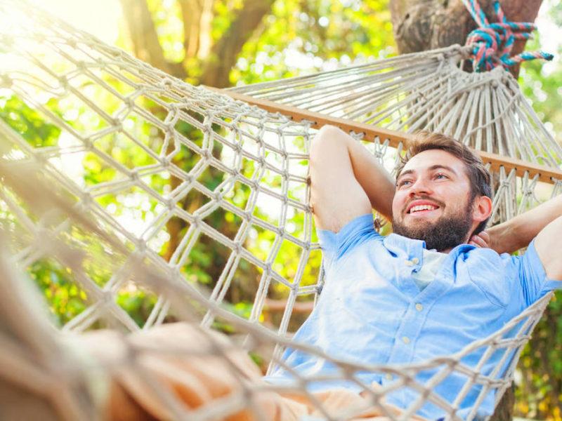photo of smiling man swinging in hammock