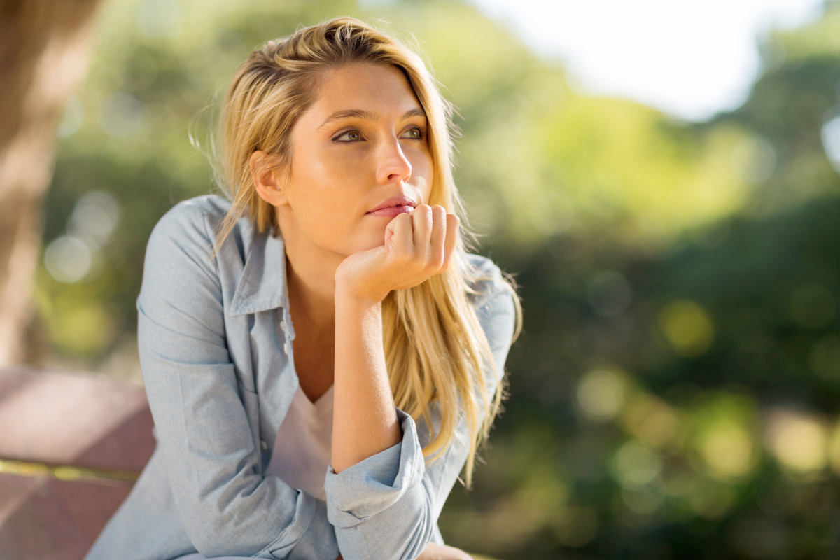 Thoughtful woman sitting alone outdoors | How To Overcome Emotional Pain Naturally
