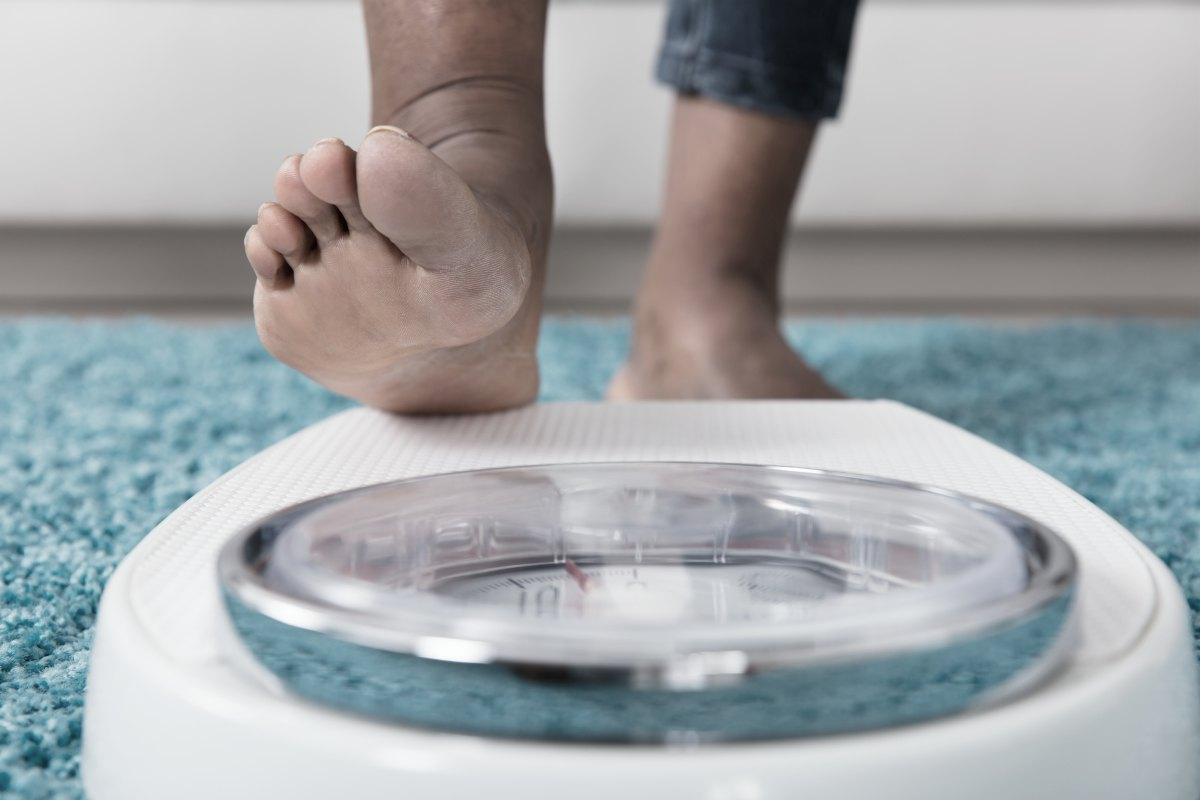 person stepping on weighing scale | The Amount Of Caffeine In Tea, Coffee, And Soda | FAQ | caffeine in tea | caffeine pills