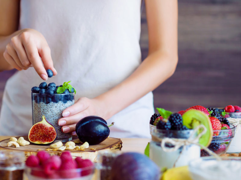 photo of woman preparing chia pudding with berries, good foods to speed up digestion