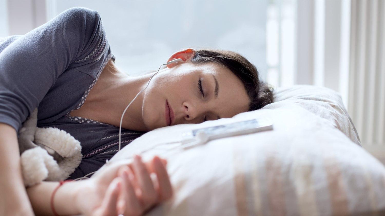 Featured | woman sleeping with earphone | Can Sleep Music Really Help You Sleep Better? (According To Science) | relaxing sleep music