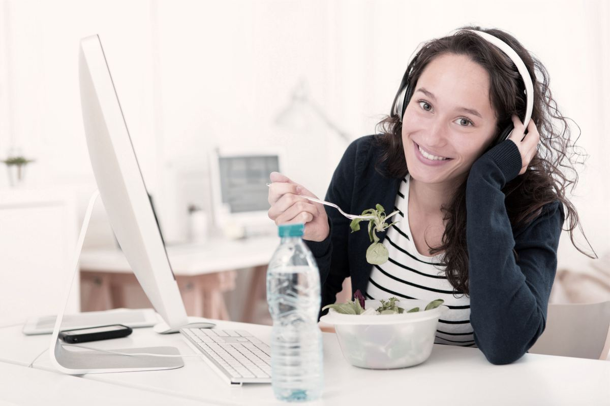 working woman eating salad while in front of desktop and listening to music | employee with headphones on break | zen music | calming music | what is zen music