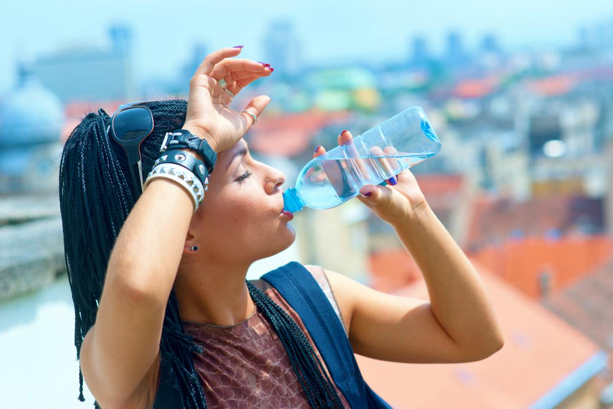 woman drinking water | How To Keep Your Gut Health Happy While Traveling | best probiotics for travel | gut healthy while traveling