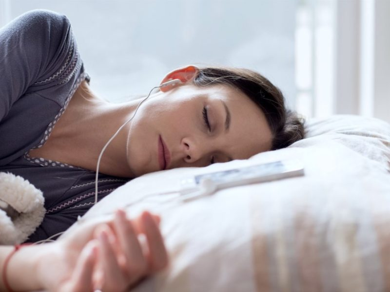 photo of woman sleeping listening to sleep music through headphones