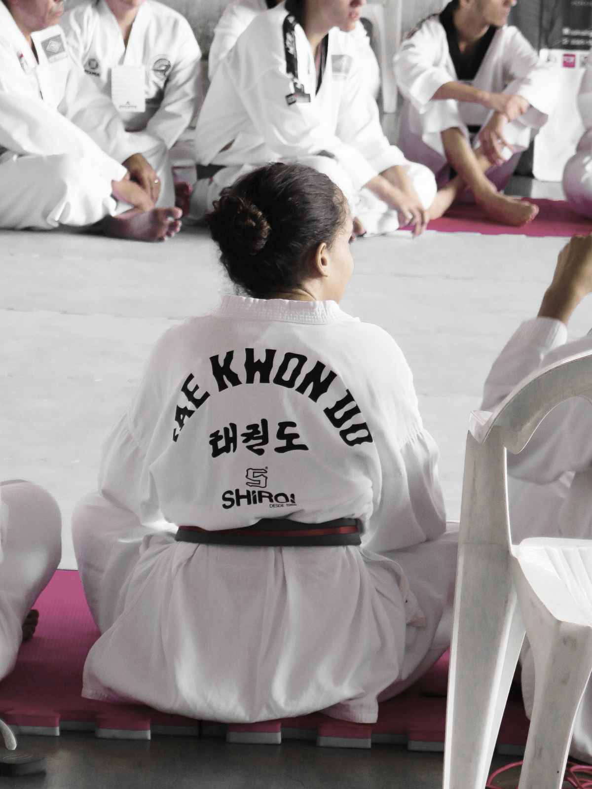 young girl wearing taekwondo uniform dobok while sitting down   types of martial arts   types of martial arts self defense   all types of martial arts