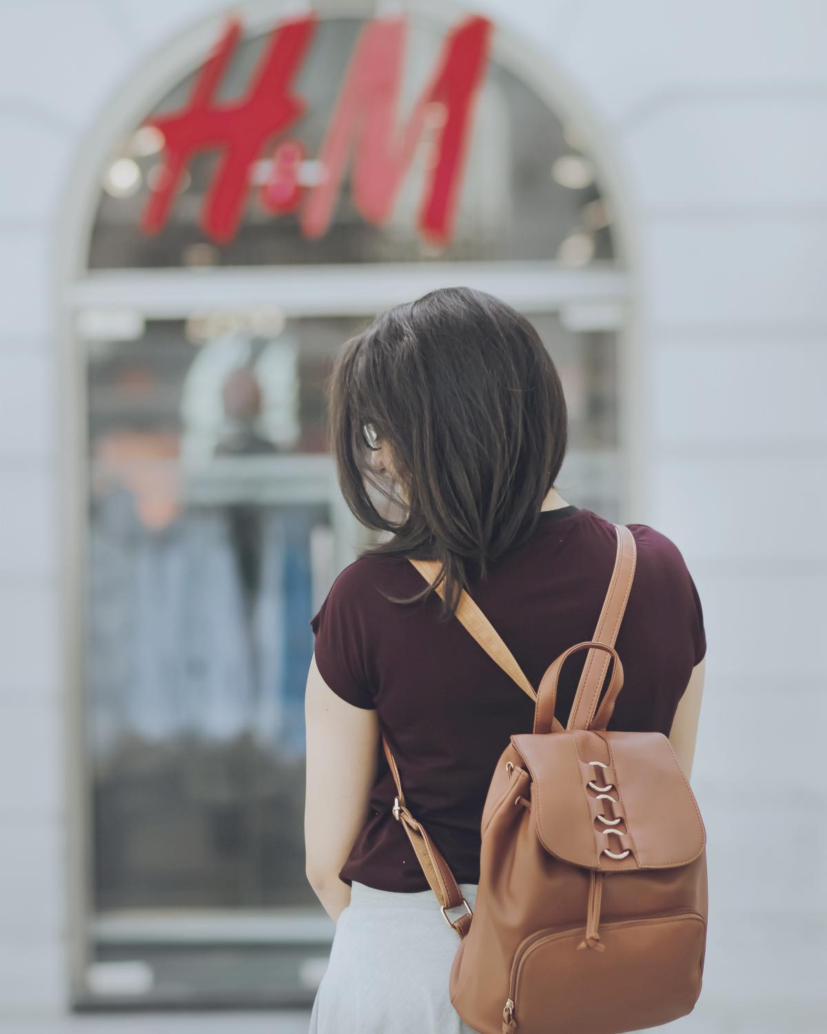 woman with bag entering H&M store | grow financial | making money | make money