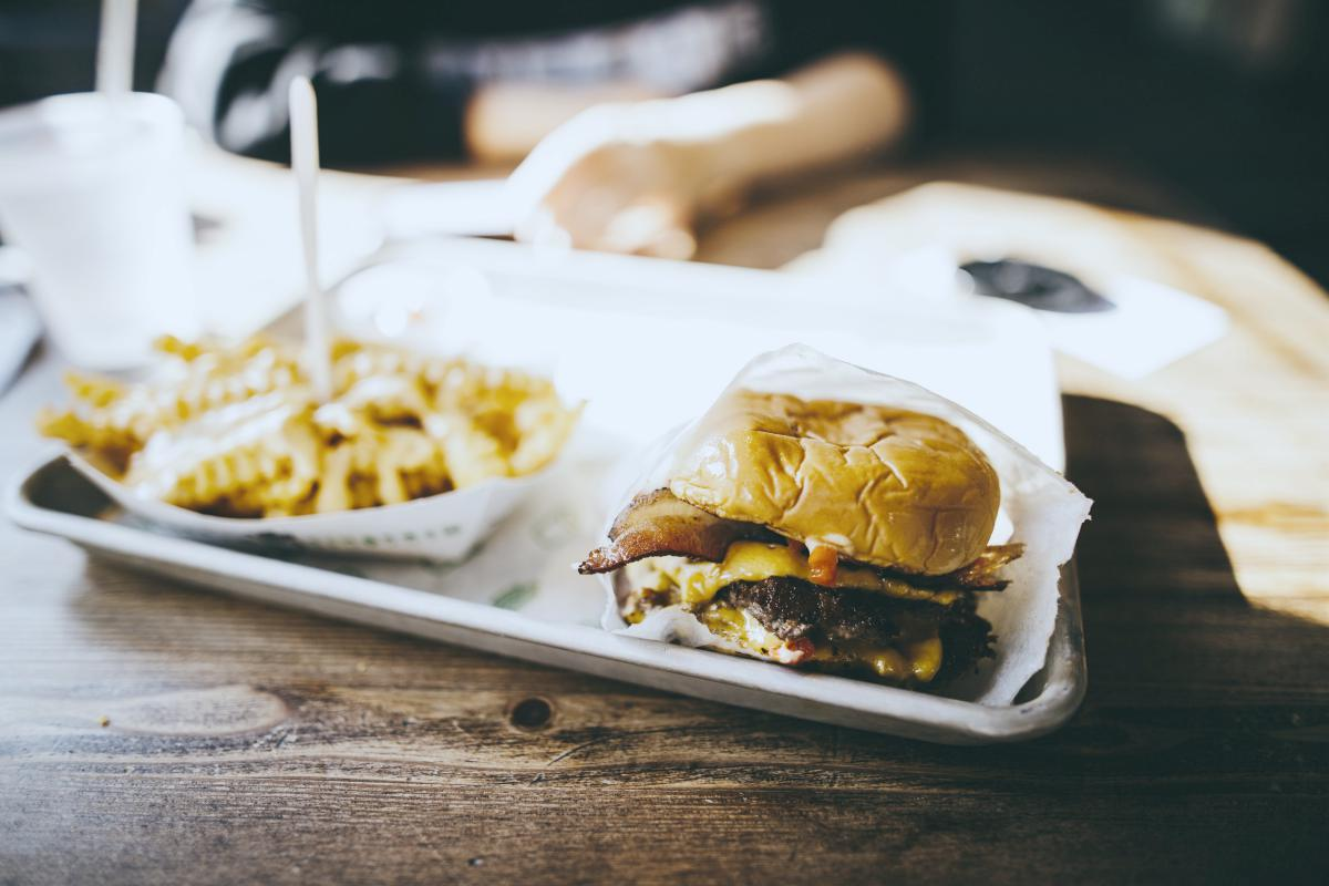 a tray on table with burger and fries   fast food   keto fast food options   fast food chains