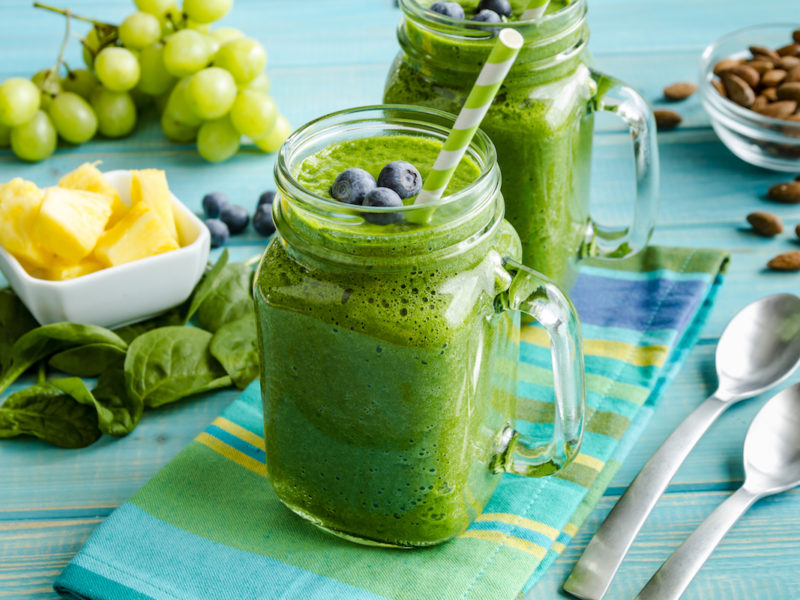 photo of a green smoothie on a table with fruit and almonds