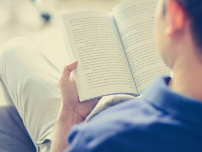 photo of man reading Cognitive Behavioral Therapy book